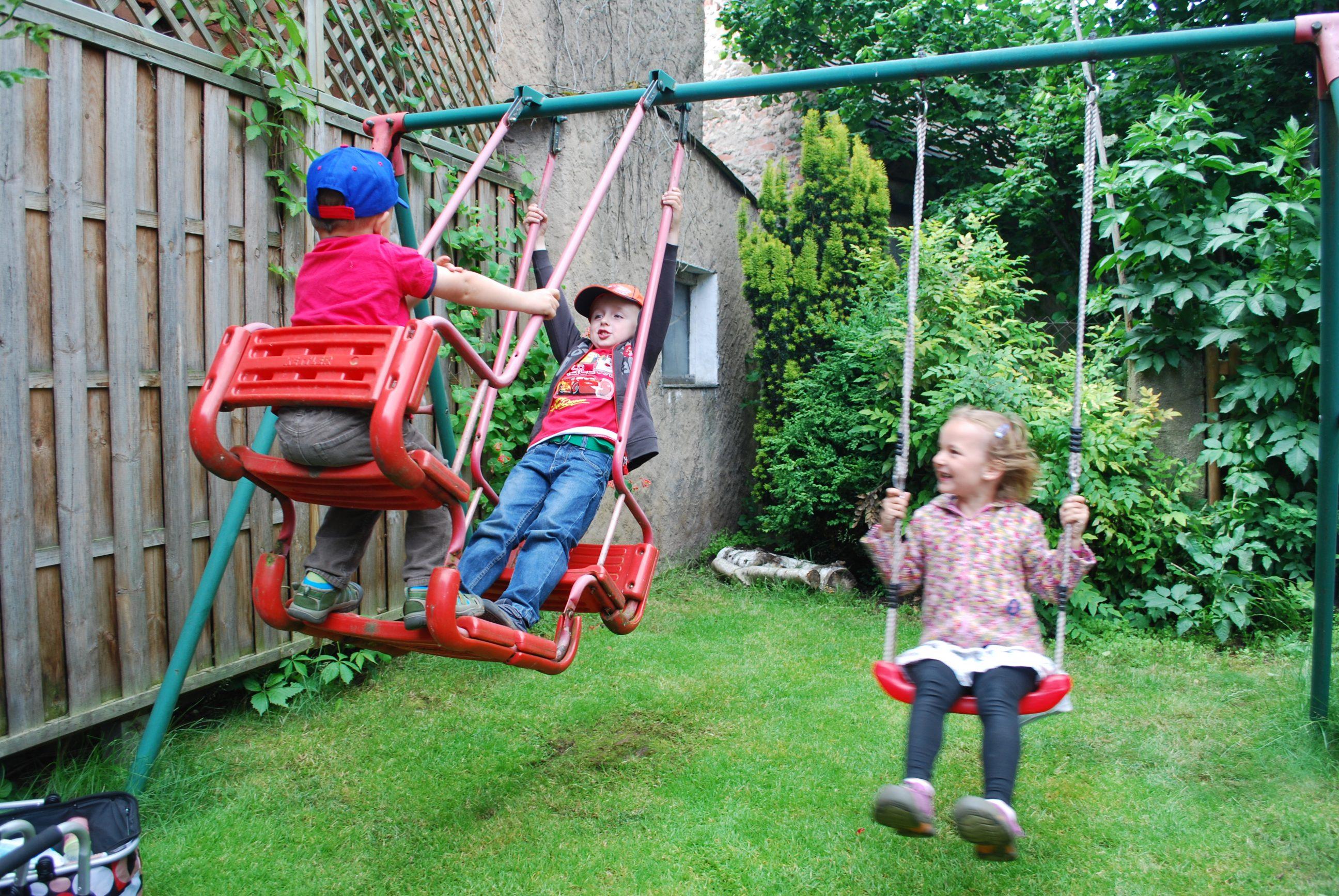 Kinder schaukeln im Garten